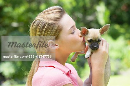 Girl kissing puppy dog Stock Photo - Premium Royalty-Free, Image code: 635-01347756