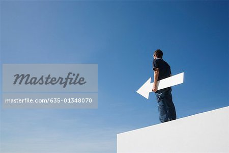 Man outdoors on wall with blank arrow Stock Photo - Premium Royalty-Free, Image code: 635-01348070