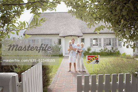 Man and woman holding babies in front of house with sold sign and white fence Stock Photo - Premium Royalty-Free, Image code: 635-01348155