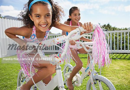 Two girls riding bicycles outdoors smiling Stock Photo - Premium Royalty-Free, Image code: 635-01488981