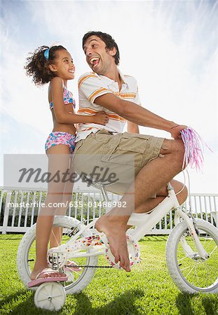 Father and daughter on bicycle with streamers smiling Stock Photo - Premium Royalty-Free, Image code: 635-01488982