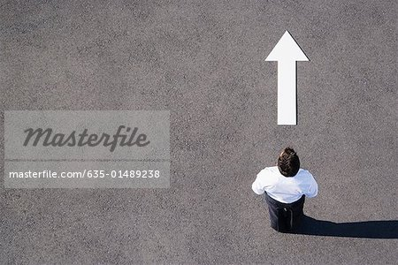 Arrow on pavement pointing away from businessman Stock Photo - Premium Royalty-Free, Image code: 635-01489238