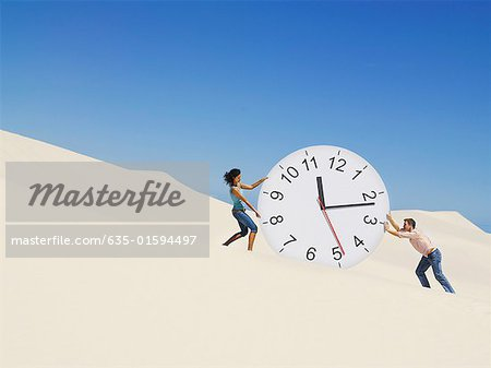 A couple pushing a clock in the desert Stock Photo - Premium Royalty-Free, Image code: 635-01594497