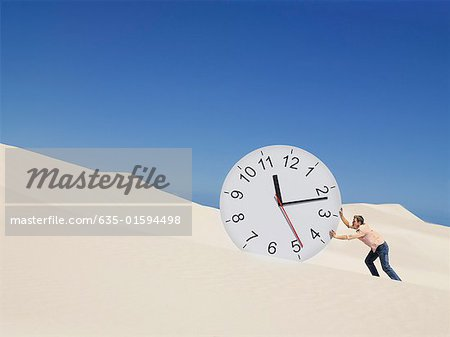 A man pushing a clock in the desert Stock Photo - Premium Royalty-Free, Image code: 635-01594498