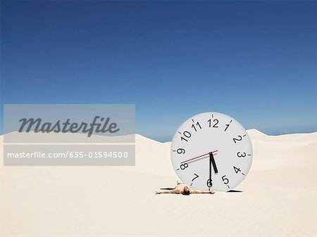 A man lying by a clock in the desert Stock Photo - Premium Royalty-Free, Image code: 635-01594500
