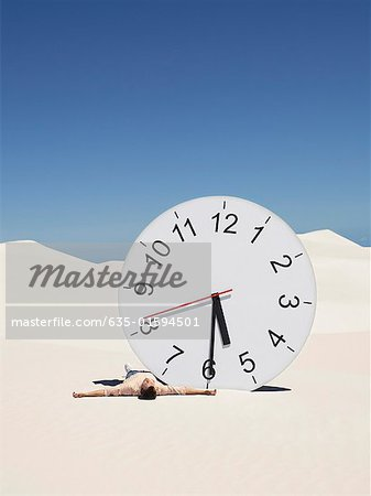 A man lying by a clock in the desert Stock Photo - Premium Royalty-Free, Image code: 635-01594501