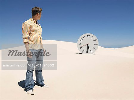 A man looking at a clock in the desert Stock Photo - Premium Royalty-Free, Image code: 635-01594502