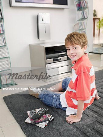 Boy in living room next to remotes and DVDs Stock Photo - Premium Royalty-Free, Image code: 635-01706267