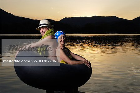 Couple in an inner tube by a lake Stock Photo - Premium Royalty-Free, Image code: 635-01707286