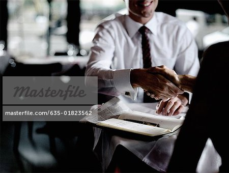 Man and woman in restaurant shaking hands Stock Photo - Premium Royalty-Free, Image code: 635-01823562