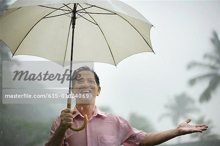 Man outdoors in rain with umbrella Stock Photo - Premium Royalty-Free, Image code: 635-01824069