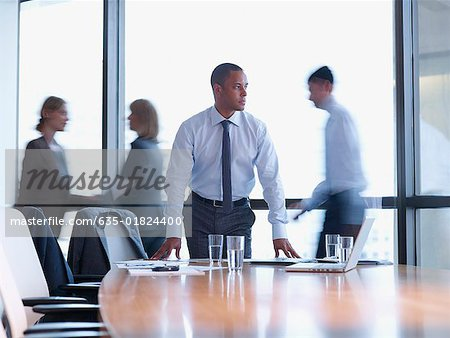 Businessman in boardroom with three co-workers behind him Stock Photo - Premium Royalty-Free, Image code: 635-01824400