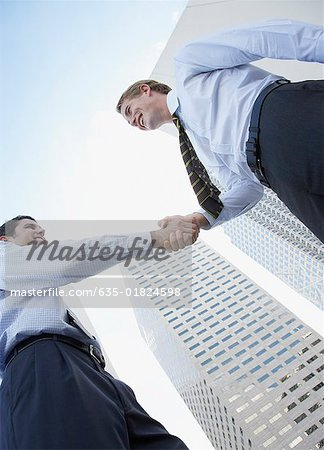 Two businessmen outdoors shaking hands Stock Photo - Premium Royalty-Free, Image code: 635-01824598