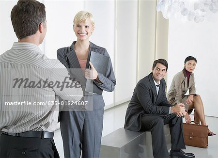 Two businesspeople shaking hands in office lobby with two businesspeople watching Stock Photo - Premium Royalty-Free, Image code: 635-01824607