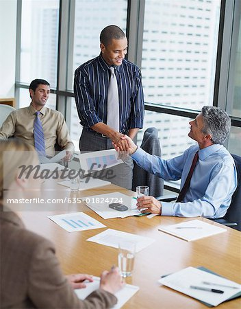 Two businessmen in boardroom shaking hands with two co-workers watching Stock Photo - Premium Royalty-Free, Image code: 635-01824724