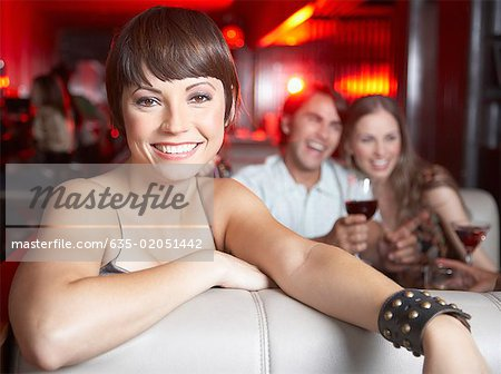 Woman sitting in booth at nightclub smiling Stock Photo - Premium Royalty-Free, Image code: 635-02051442