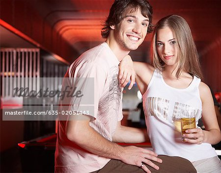 Couple by pool tables with beverage smiling Stock Photo - Premium Royalty-Free, Image code: 635-02051443