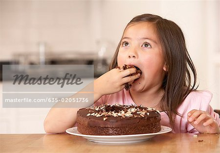 Young girl in kitchen being messy eating cake Stock Photo - Premium Royalty-Free, Image code: 635-02051736