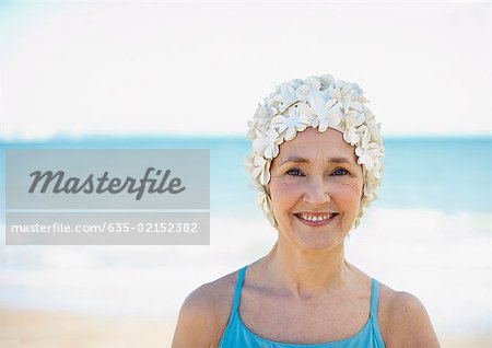 Mature woman in old-fashioned swim cap on beach Stock Photo - Premium Royalty-Free, Image code: 635-02152382