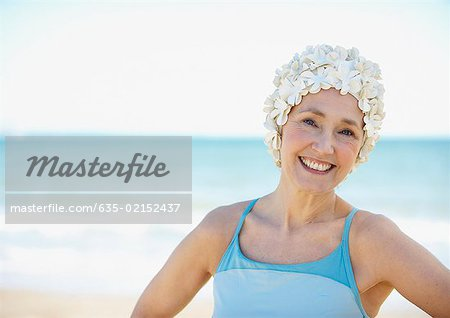 Mature woman in old-fashioned swim cap on beach Stock Photo - Premium Royalty-Free, Image code: 635-02152437