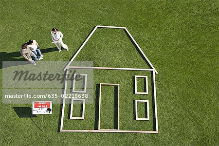 "People standing near ""for sale"" sign and house outline Stock Photo - Premium Royalty-Free, Image code: 635-02218638"