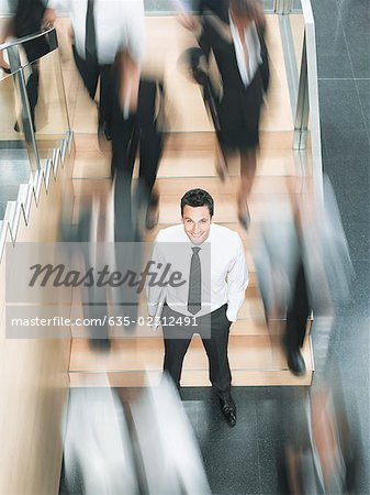 Calm businessman standing in busy office Stock Photo - Premium Royalty-Free, Image code: 635-02312491
