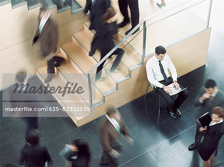 Businessman working in busy office corridor Stock Photo - Premium Royalty-Free, Image code: 635-02312535