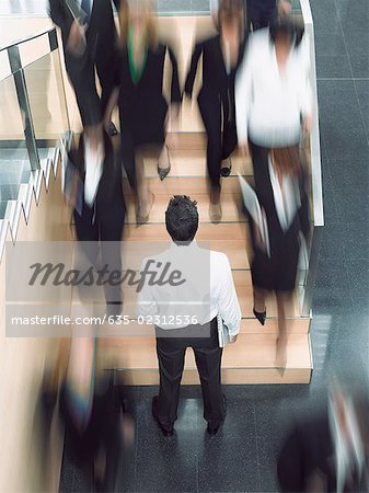 Businessman looking up busy office staircase Stock Photo - Premium Royalty-Free, Image code: 635-02312536