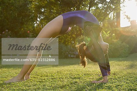 Girl doing backbend on grass Stock Photo - Premium Royalty-Free, Image code: 635-02312886