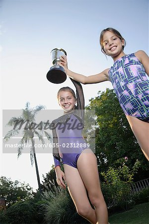 Young gymnasts holding trophy Stock Photo - Premium Royalty-Free, Image code: 635-02312889