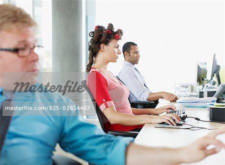 Businesswoman working and wearing curlers at desk Stock Photo - Premium Royalty-Free, Image code: 635-02614447