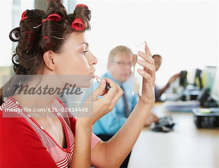 Businesswoman in curlers applying lipstick at desk Stock Photo - Premium Royalty-Free, Image code: 635-02614448