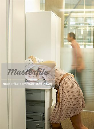 Businesswoman photocopying her head Stock Photo - Premium Royalty-Free, Image code: 635-02614520