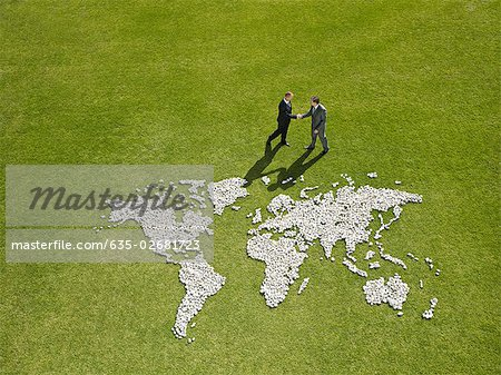 Businessmen shaking hands near world map made of rocks Stock Photo - Premium Royalty-Free, Image code: 635-02681723