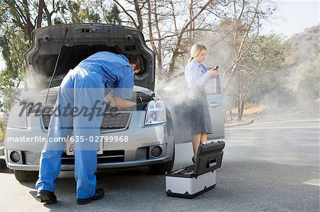Businesswoman using cell phone while mechanic looks at car engine Stock Photo - Premium Royalty-Free, Image code: 635-02799968