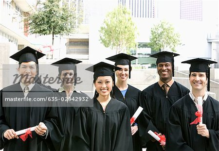 Graduates in caps and gowns with diplomas Stock Photo - Premium Royalty-Free, Image code: 635-02942932