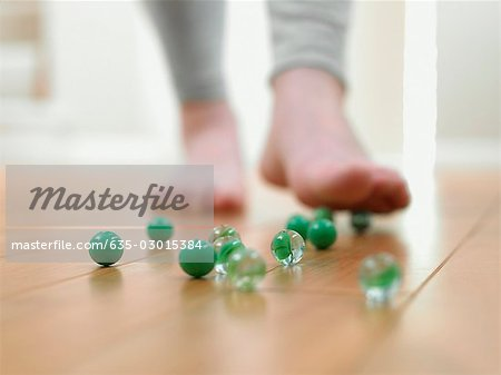Child about to slip on marbles on the floor Stock Photo - Premium Royalty-Free, Image code: 635-03015384