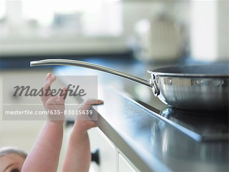 Baby reaching for hot frying pan on stove Stock Photo - Premium Royalty-Free, Image code: 635-03015639