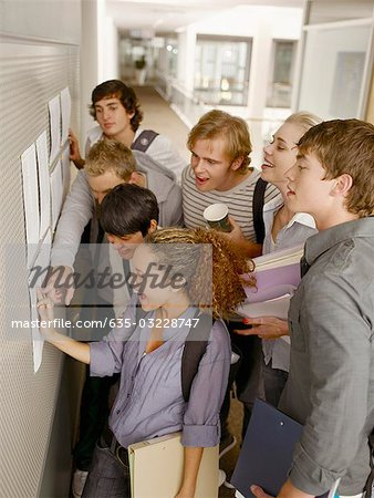 College students checking test scores in corridor Stock Photo - Premium Royalty-Free, Image code: 635-03228747