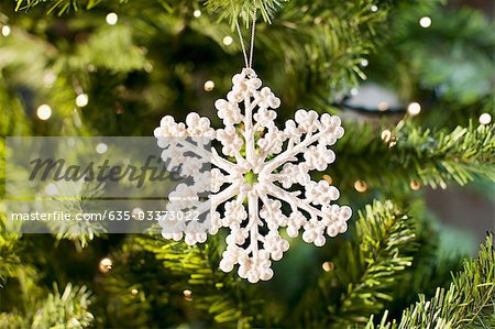 Snowflake Christmas ornament on tree Stock Photo - Premium Royalty-Free, Image code: 635-03373022