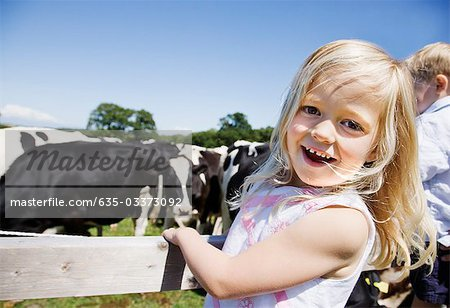 Girl at fence near cows Stock Photo - Premium Royalty-Free, Image code: 635-03373092