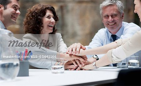 Business people stacking hands in meeting Stock Photo - Premium Royalty-Free, Image code: 635-03441166