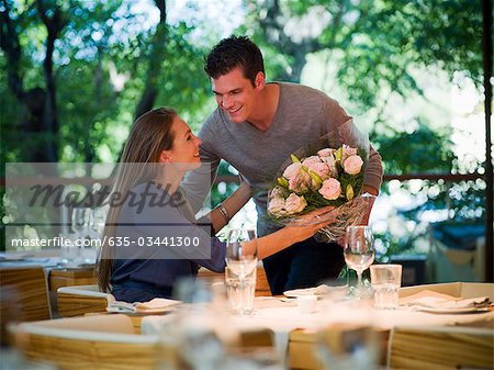 Man giving flowers to woman at restaurant table Stock Photo - Premium Royalty-Free, Image code: 635-03441300