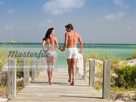 Couple in bathing suits holding hands and walking toward ocean Stock Photo - Premium Royalty-Free, Image code: 635-03441310