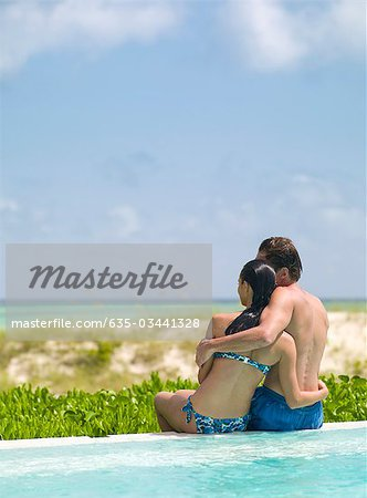 Couple sitting at edge of swimming pool, hugging and looking at ocean Stock Photo - Premium Royalty-Free, Image code: 635-03441328