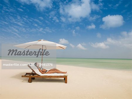 Woman laying on lounge chair under beach umbrella Stock Photo - Premium Royalty-Free, Image code: 635-03441376
