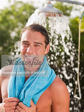 Man with towel around neck near outdoor shower head Stock Photo - Premium Royalty-Free, Image code: 635-03441379