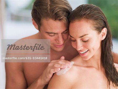 Man applying lotion to woman's shoulder Stock Photo - Premium Royalty-Free, Image code: 635-03441418