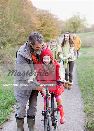 Family riding bicycles in park Stock Photo - Premium Royalty-Free, Image code: 635-03457388