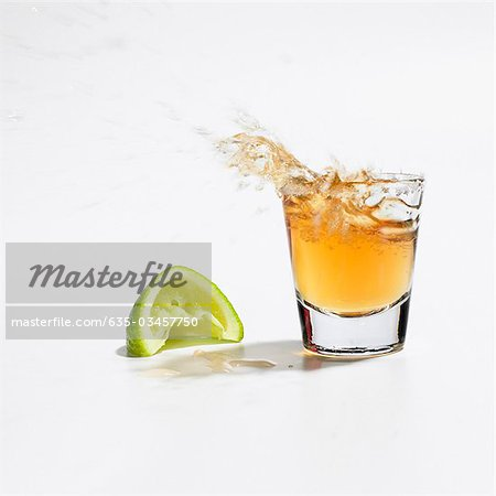 Close up of tequila splashing out of glass Stock Photo - Premium Royalty-Free, Image code: 635-03457750